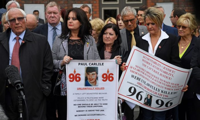 Trevor Hicks (L), whose two daughters Sarah and Victoria died in the 1989 Hillsborough disaster, stands with campaigners outside Parr Hall after family members affected by the 1989 Hillsborough stadium disaster were informed of the charging decisions by the Hillsborough CPS, in Warrington, east of Liverpool on June 28, 2017. (PAUL ELLIS/AFP/Getty Images)