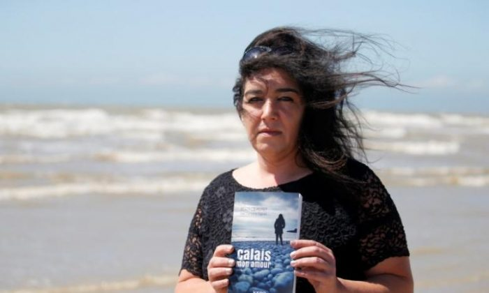 """Beatrice Huret poses with her book titled """"Calais Mon Amour"""" as she walks on the beach of Dannes near Boulogne-sur-Mer, on the northern French coast, France on June 15, 2017. (REUTERS/Pascal Rossignol)"""