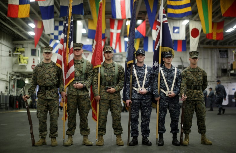 A flag party of U.S. Marines and Navy personnel take part in a ceremony marking the start of Talisman Saber 2017, a biennial joint military exercise between the United States and Australia aboard the USS Bonhomme Richard amphibious assault ship on the the Pacific Ocean off the coast of Sydney, Australia, June 29, 2017.    REUTERS/Jason Reed