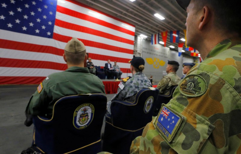 A member of the Australian Army sits in the audience alongside a U.S. flag as the backdrop of a ceremony marking the start of Talisman Saber 2017, a biennial joint military exercise between the United States and Australia, aboard the USS Bonhomme Richard amphibious assault ship on the the Pacific Ocean off the coast of Sydney, Australia, June 29, 2017. REUTERS/Jason Reed