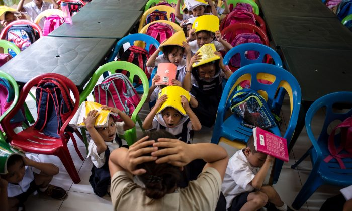 Schoolchildren from the Corazon Aquino Elementary School participate in a nationwide earthquake drill in Manila on June 29, 2017.