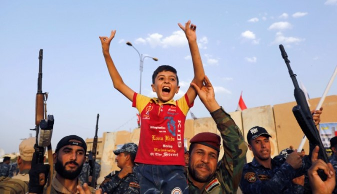 Members of Iraqi Federal Police carry a boy as they celebrate victory of military operations against the Islamic State militants  in West Mosul, Iraq, July 2, 2017. (REUTERS/Erik De Castro)