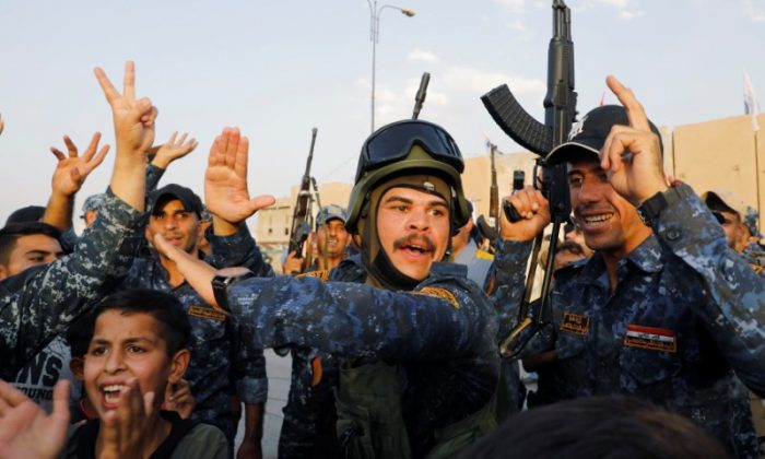 Members of Iraqi Federal Police dance and sing as they celebrate victory of military operations against the Islamic State militants  in West Mosul, Iraq, July 2, 2017. (REUTERS/Erik De Castro)
