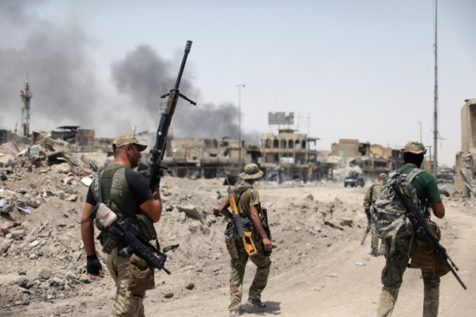 Members of the Emergency Response Division walk with their weapons during the fight with the Islamic States militants in the Old City of Mosul, Iraq, July 3, 2017. (REUTERS/Ahmed Jadallah)