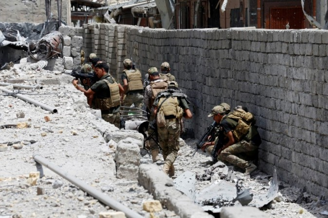 Members of the Emergency Response Division walk with their weapons during the fight with the Islamic States militants in the Old City of Mosul. (REUTERS/Ahmed Jadallah)