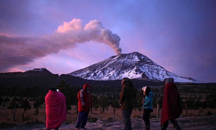 TOPSHOT - People look at the Popocatepetl volcano as it spews ash from Paso de Cortes, Puebla, Mexico on January 24, 2016. In the last hours, the monitoring system of the Popocatepetl volcano registered some explosions with large emissions of steam, gas and ash. The alert level is yellow, phase II. (PABLO SPENCER/AFP/Getty Images)