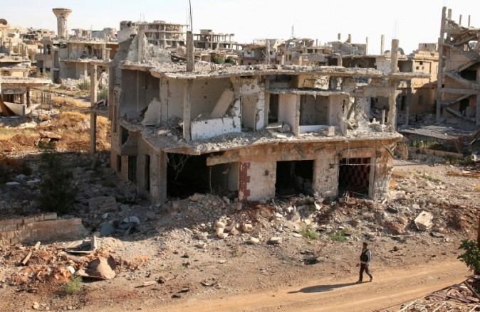 A rebel fighter walks past damaged buildings in a rebel-held part of the southern city of Deraa, Syria on June 22, 2017. (REUTERS/Alaa Al-Faqir)