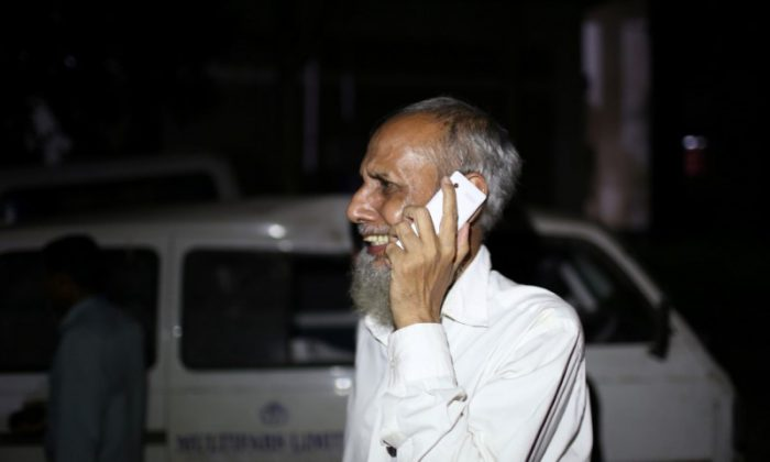 A man, who lost his daughter-in-law, cries while talking on the phone following a deadly boiler blast inside a garment factory in Gazipur, Bangladesh, July 4, 2017. (Reuters/Probal Rashid)