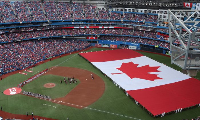 A general view of Rogers Centre as a large Canadian flag is unfurled in the outfield on Canada Day during the playing of the Canadian national anthem before the start of the Toronto Blue Jays MLB game against the Boston Red Sox at Rogers Centre in Toronto, Canada on July 1, 2017. (Tom Szczerbowski/Getty Images)