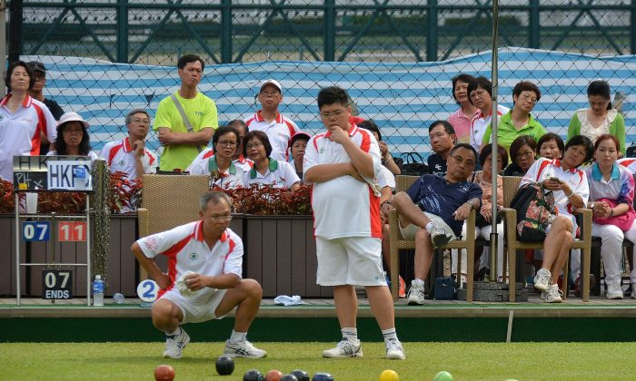 Hong Kong Football Club's Anthony Yip (standing) on his way to defeating Esmond Lee from Phoenix in the final of the Reunification Cup on July 2. Stephanie Worth)