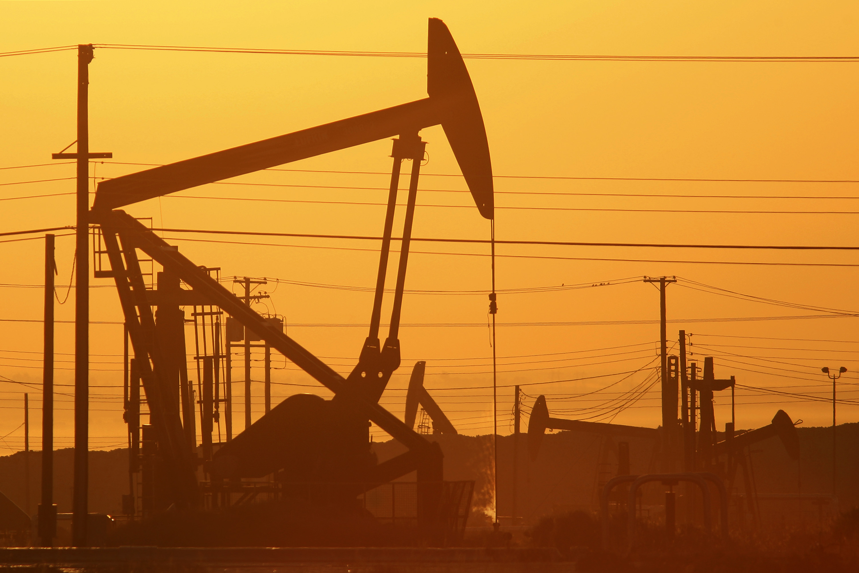Pump jacks are seen at dawn in an oil field over the Monterey Shale formation where gas and oil extraction using hydraulic fracturing, or fracking, is on the verge of a boom on March 24, 2014 near Lost Hills, California. (David McNew/Getty Images)