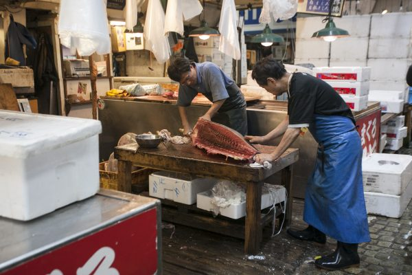 Fishermen slice up a fish at the Tsukiji market. (Annie Wu/The Epoch Times)