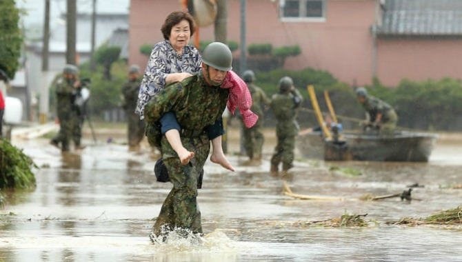 Japanese soldiers help local residents evacuate from flooded area in Asakura, Fukuoka prefecture. (STR/AFP/Getty Images)
