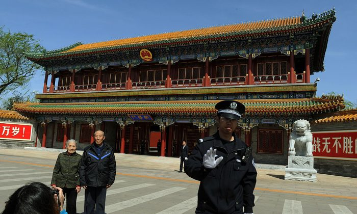 A Chinese policeman asks not to take pictures outside Zhongnanhai which serves as the central headquarters for the Communist Party of China after the sacking of politician Bo Xilai from the countries powerful Politburo, in Beijing on April 11, 2012. (MARK RALSTON/AFP/Getty Images)