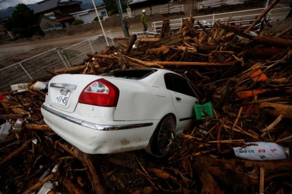 Debris and a car which were swept by heavy rain are seen in Asakura, Fukuoka Prefecture, Japan July 8, 2017. (Reuters/Issei Kato)