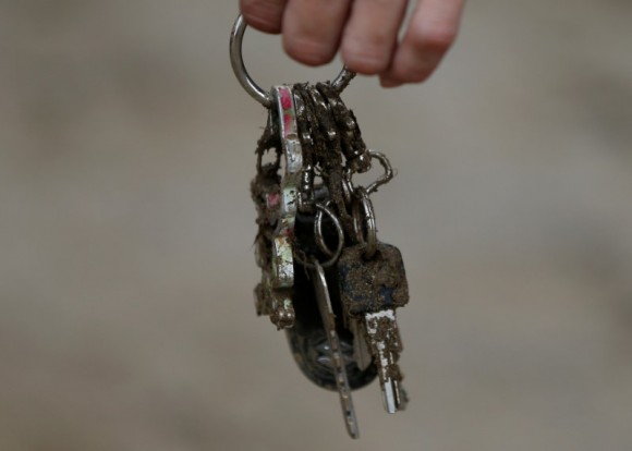A local resident holds a muddy key holder which he found from his mud covered house at an area hit by heavy rain in Asakura, Fukuoka Prefecture, Japan July 8, 2017. (Reuters/Issei Kato)