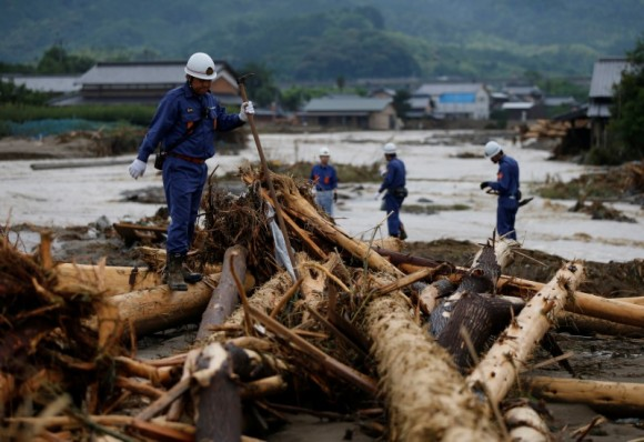 Police officers walk on woody debris which were swept by heavy rain as they conduct rescue and search operation in Asakura, Fukuoka Prefecture, Japan July 8, 2017. (Reuters/Issei Kato)
