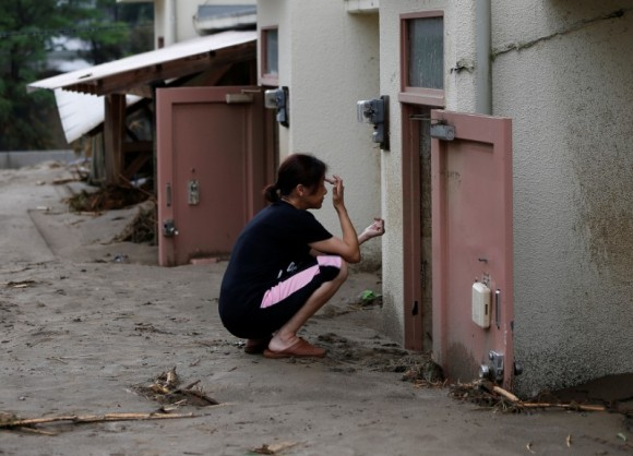 A local resident sits in front of mud covered door of her room as she looks for her personal belongings at an area hit by heavy rain in Asakura, Fukuoka Prefecture, Japan July 8, 2017. (Reuters/Issei Kato)