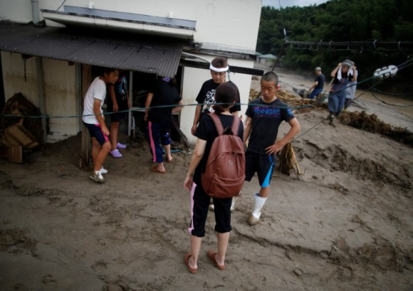 Local resident Mamoru Fujiwara and his family members look for their personal belongings at their mud-covered house at an area hit by heavy rain in Asakura, Fukuoka Prefecture, Japan July 8, 2017. (Reuters/Issei Kato)