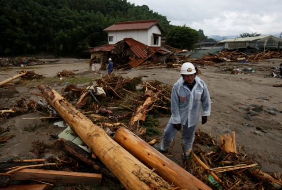 Police officers walk on woody debris which were swept by heavy rain as they conduct a rescue and search operation in Asakura, Fukuoka Prefecture, Japan July 8, 2017. (Reuters/Issei Kato)