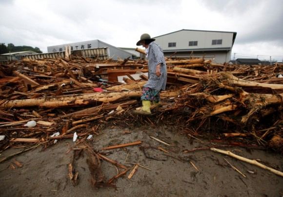 A local resident walks on woody debris which were swept by heavy rain in Asakura, Fukuoka Prefecture, Japan July 8, 2017. (Reuters/Issei Kato)
