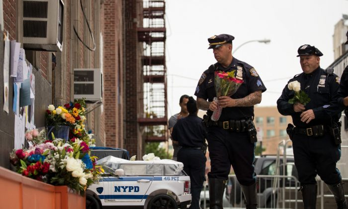 Members of the New York City Police Department arrive with flowers at a makeshift memorial for fallen NYPD officer Miosotis Familia outside the 46th Police Precinct, July 6, 2017. (Photo by Drew Angerer/Getty Images)
