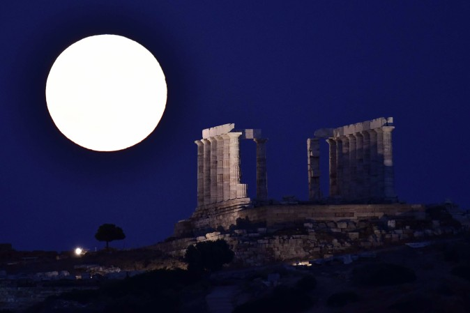 The full moon rises by the ancient temple of Poseidon (Neptun) at cape Sounio, some 65 km southeast of Athens, Greece, on July 9, 2017. (LOUISA GOULIAMAKI/AFP/Getty Images)