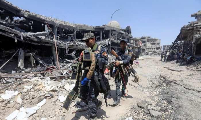 Members of Iraqi Federal police carry suicide belts used by Islamic State militants in the Old City of Mosul, Iraq. (Reuters/Alaa Al-Marjani)