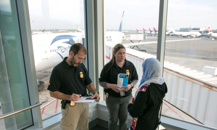 Agents from Homeland Security Investigations speak to a 14-year-old American citizen about female genital mutilation as she is about to fly alone to Egypt at JFK International Airport in New York on June 26, 2017. The agents are concerned the young girl may be subject to female genital mutilation once in Egypt. (Benjamin Chasteen/The Epoch Times)