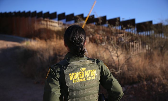 U.S. Border Patrol agent Nicole Ballistrea watches over the U.S.-Mexico border fence on December 9, 2014 in Nogales, Arizona. (John Moore/Getty Images)