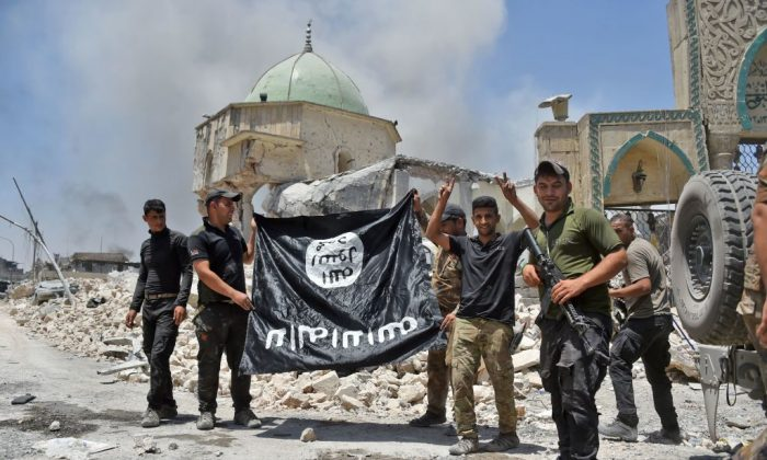 A member of the Iraqi Counter-Terrorism Service (CTS) raises the victory gesture as others hold upside-down the black flag of the Islamic State (IS) group, outside the destroyed Al-Nuri Mosque in the Old City of Mosul, after the area was retaken from IS, on June 30, 2017.