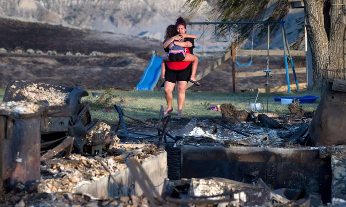 Kelsey Thorne holds her daughter Nevaeh Porter as she views the remains of the home where they lived with her parents on the Ashcroft First Nation reserve that was destroyed by wildfire, near Ashcroft, B.C., July 9, 2017. (The Canadian Press/Darryl Dyck)