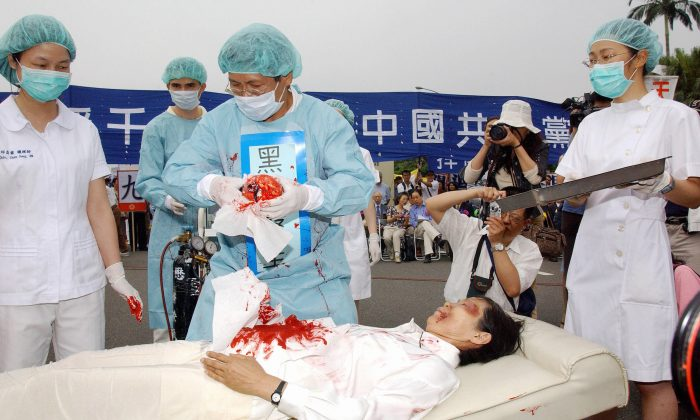 During a rally joined by thousands of Falun Gong practitiioners at Taipei 23 April 2006, four demonstrators play in an action drama against what they said was the Chinese communists' killing of Falun Gong followers and harvesting of their organs in concentration camps.  (PATRICK LIN/AFP/Getty Images)