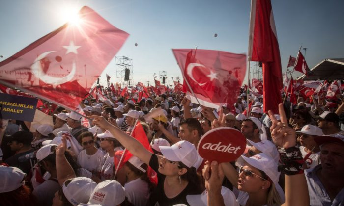"Thousands of supporters cheer and wave flags while listening to Turkey's main opposition Republican People's Party (CHP) leader Kemal Kilicdaroglu speak on stage during the ""Justice Rally"" in Istanbul, Turkey on July 9, 2017. (Chris McGrath/Getty Images)"