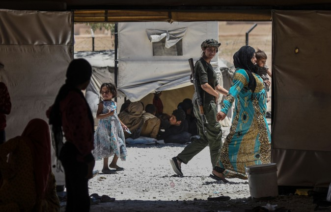 A female fighter from the Kurdish Women's Protection Units walks among Syrians who fled the countryside surrounding the ISIS stronghold of Raqqa at a refugee camp in the village of Ayn Issa, Syria, on July 11, 2017. (BULENT KILIC/AFP/Getty Images)