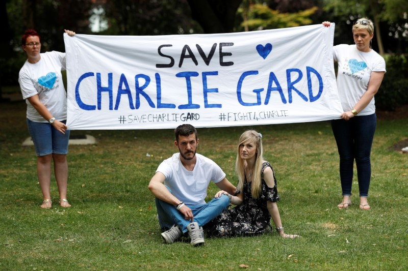 Connie Yates and Chris Gard, pose for photographers as supporters hold a banner, before delivering a petition to Great Ormond Street Hospital, in central London, Britain July 9, 2017. (REUTERS/Peter Nicholls)