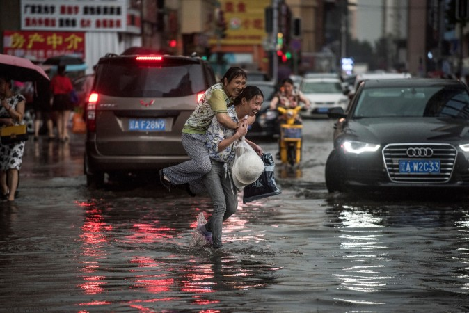 A woman holds an elderly woman on her back to cross a flooded street after heavy rain in Shenyang, China, on July 14, 2017. (FRED DUFOUR/AFP/Getty Images)