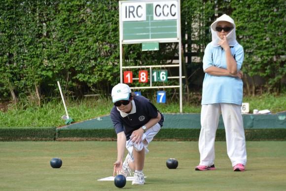 FOCUS – Shirley Ko (Standing at the back) of Indian Recreation Club considering her options for her last bowl while her opponent Angel So is delivering her second.  Ko was leading on the board by two shots but down three on the green. She decided to go heavy but narrowly missed. The Craigengower Cricket Club team won the game by a single shot. (Stephanie Worth)
