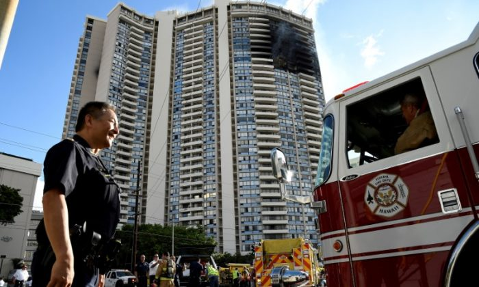 A police officer directs a fire truck at the Marco Polo apartment building after a fire broke out in it in Honolulu, Hawaii, July 14, 2017.  (Reuters/Hugh Gentry)