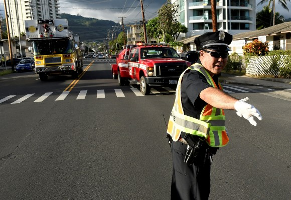 A police officer directs a fire truck to the Marco Polo apartment building after a fire broke out in it in Honolulu, Hawaii, July 14, 2017.  (Reuters/Hugh Gentry)