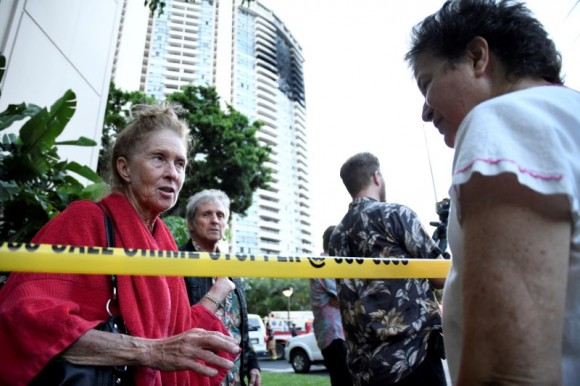 Karen Hastings (L), who was evacuated from the floors where the fire broke out at Marco Polo apartment building, talks with another resident, in Honolulu, Hawaii, July 14, 2017. (Reuters/Hugh Gentry)