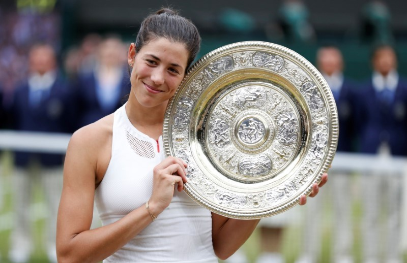Spain's Garbine Muguruza poses with the trophy as she celebrates winning the final against Venus Williams of the U.S. (REUTERS/Matthew Childs)