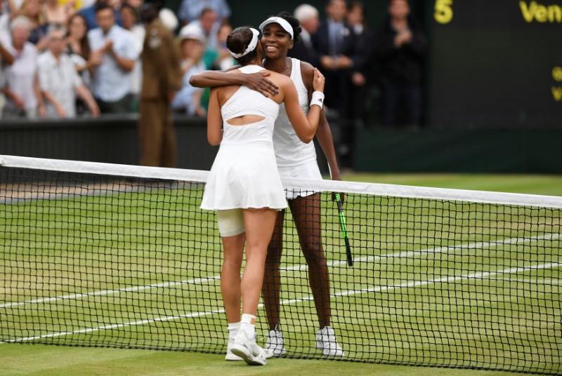 Tennis - Wimbledon - London, Britain - July 15, 2017   Spain's Garbine Muguruza with Venus Williams of the U.S. after winning their final match   REUTERS/Tony O'Brien