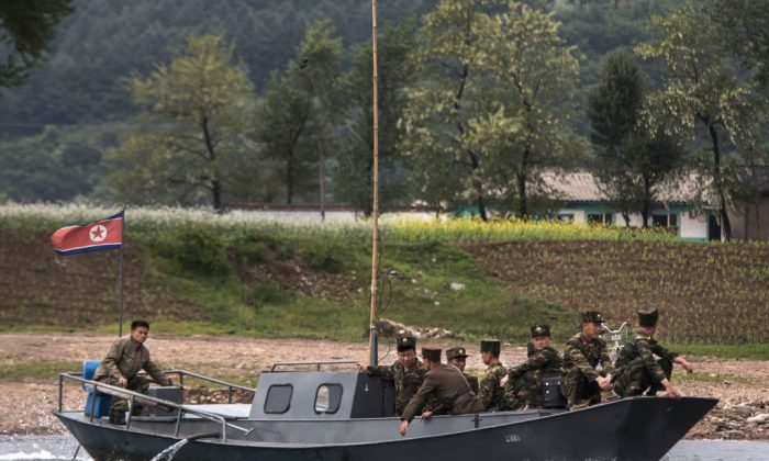 North Korean soldiers ride on a boat used as a local ferry. (Photo by Kevin Frayer/Getty Images)