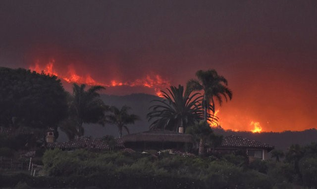 Flames from the Whittier Fire burn in the distance behind a home near El Capitan Ranch near Santa Barbara, California, U.S. July 14, 2017. Picture taken July 14, 2017. (Mike Eliason/Santa Barbara County Fire Department/Handout via Reuters)