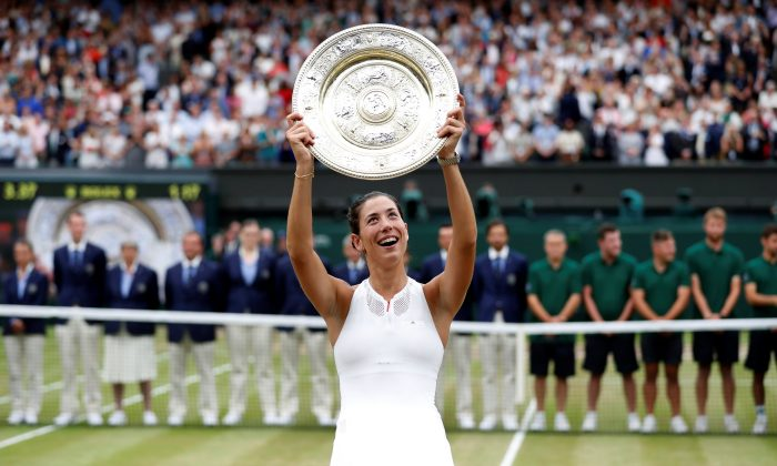 Spain's Garbine Muguruza poses with the trophy as she celebrates winning the final against Venus Williams of the U.S. at Wimbledon in London, July 15, 2017. (Reuters/Matthew Childs)