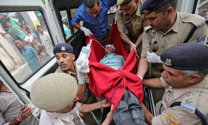 A man who was injured after a bus he was travelling in skidded off a mountain road and fell into a gorge in Jammu and Kashmir's Ramban district, is rushed to a hospital for treatment in Jammu, July 16, 2017. (Reuters/Mukesh Gupta)