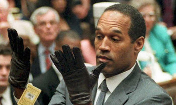 Former U.S. football player and actor O.J. Simpson looking at a new pair of Aris extra-large gloves that prosecutors had him put on during his double-murder trial in Los Angeles on June 21, 1995. (VINCE BUCCI/AFP/Getty Images)
