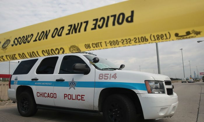 Police investigate the murder of a young man found shot to death in the back seat of a bullet-riddled car on June 30, 2017 in Chicago, Illinois. (Scott Olson/Getty Images)