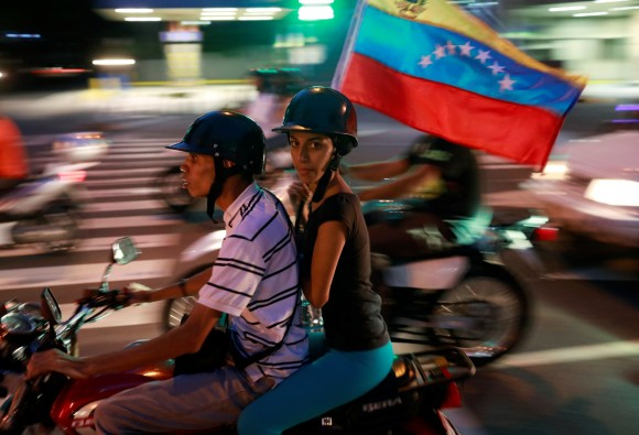 Opposition supporters ride on a motorcycle after an unofficial plebiscite against President Nicolas Maduro's government and his plan to rewrite the constitution, in Caracas, Venezuela July 16, 2017. (Reuters/Marco Bello)